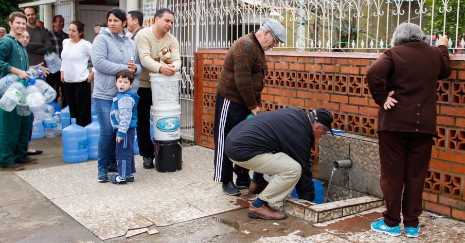 23.jul.2015 - Moradores recolhem água de uma bica em Alvorada, no Rio Grande do Sul. A cidade, afetada pelas chuvas dos últimos dias, sofre com a falta de água potável desde o início da semana