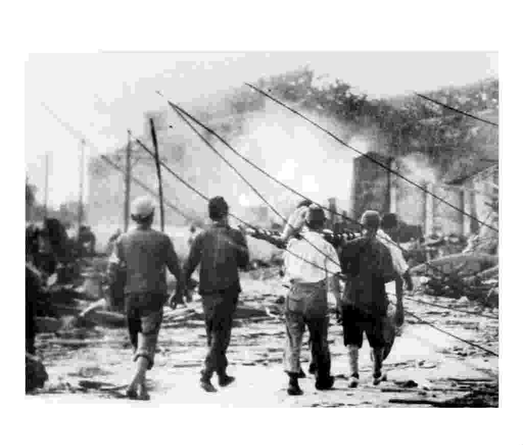 """29.jul.2015 - Equipe de busca carrega uma vítima da bomba atômica que atingiu Hiroshima, no Japão, em 6 de agosto de 1945. Ironicamente batizada de """"little boy"""", (garotinho, em inglês), a bomba lançada na cidade é até hoje a arma que mais mortes provocou em pouco tempo, matando 80 mil pessoas instantaneamente. Sua potência correspondia a 20 mil toneladas de dinamite. A explosão provocou um calor de cerca de 5,5 milhões de graus centígrados, similar à temperatura do Sol - EFE"""