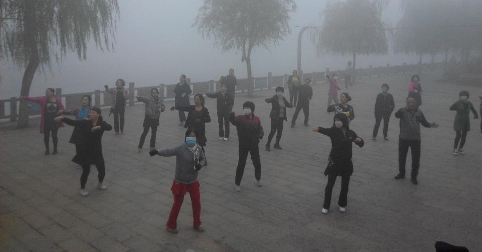 6.out.2015 - Moradores usam máscaras para o exercício matinal em Pingquan, provincia de Hebei, norte de China, a 300 quilómetros da capital. Autoridades chinesas emitiram alerta amarelo para Pequim e regiões vizinhas por causa da contaminação do ar