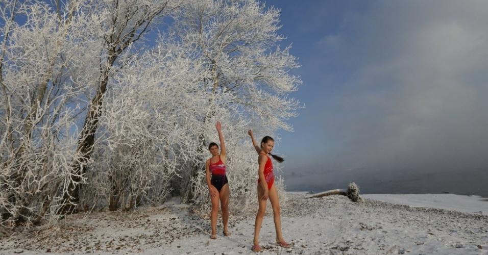 """6.jan.2015 - Nastya Usachyova, 9, e sua mãe Natalia, 39, integrantes do clube Cryophile de nadadores de inverno, se aquecem antes de nadarem no rio Yenisei, na cidade russa de Krasnoyarsk, localizada na região da Sibéria. """"Na primeira vez senti frio. Mas superei isso"""", diz Nastya. """"Muitos dos meus amigos dizem que é impossível nadar no rio Yenisei no inverno"""", afirma. A garota, cuja mãe é campeã mundial de natação de inverno, nada em águas geladas desde os dois anos de idade"""