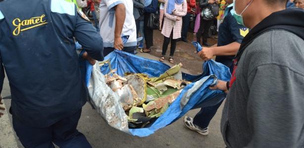 Equipes de resgate carregam destroços de Super Tucano que caiu em área residencial em Malang, na Indonésia - Aman Rochman/AFP