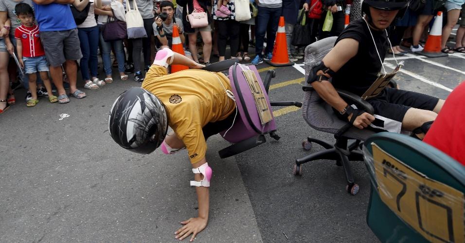 24.abr.2016 - Nessa corrida maluca, os tombos são inevitáveis. Na foto, o participante cai enquanto tenta deslocar a cadeira de escritório durante o ISU-1 Grand Prix, em Tainan, sul de Taiwan, na China