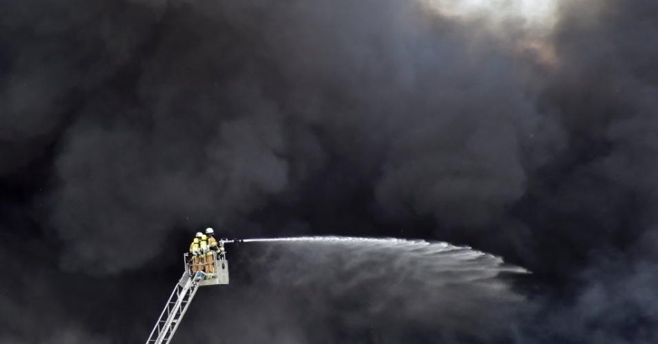11.mai.2016 - Bombeiro tenta conter incêndio de grandes proporções em Berlim, na Alemanha. Um depósito no shopping Dong Xuan pegou fogo e deu trabalho para equipes de combate. A fumaça afetou vários bairros da cidade, e autoridades aconselharam os cidadãos a manterem janelas e portas fechadas