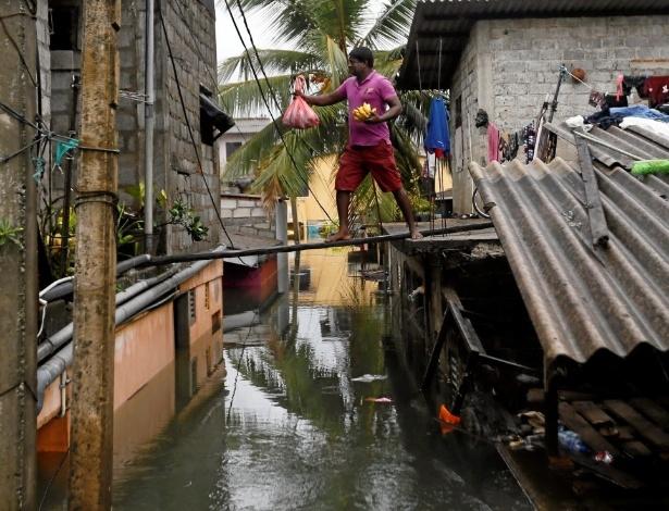 21.mai.2016 - Homem caminha sobre uma prancha de madeira sobre área inundada por enchente em Wellampitiya, Sri Lanka, neste sábado, após temporal. As chuvas que atingem o Sri Lanka neste fim de semana são as mais pesadas em 25 anos, e já causaram a morte de mais de 60 pessoas