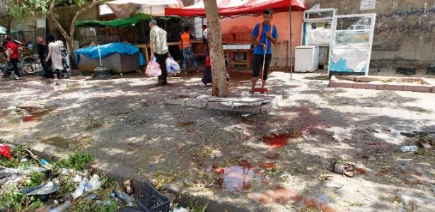 Homem limpa o chão ensanguentado do local do atentado, reivindicado pelo Estado Islâmico