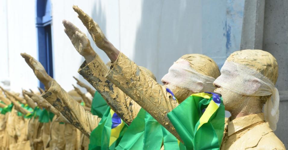 3.set.2016 - Com os olhos vendados e segurando a bandeira do Brasil com a boca, atores se cobrem de lama durante o 31º Festivale (Festival de Teatro de São José dos Campos) em um protesto silencioso a favor da democracia e contra o governo do presidente Michel Temer (PMDB), em São José dos Campos (SP)