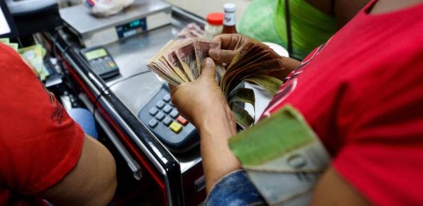 20.out.2016 - Mulher conta as muitas notas para pagar por compras em supermercado estatal na favela San José, em Caracas (Venezuela)