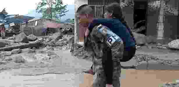 1º.abr.2017 - Soldado presta socorro a criança em local atingido por deslizamento de terra, em Mocoa, na Colômbia - Presidencia de Colombia/Xinhua - Presidencia de Colombia/Xinhua