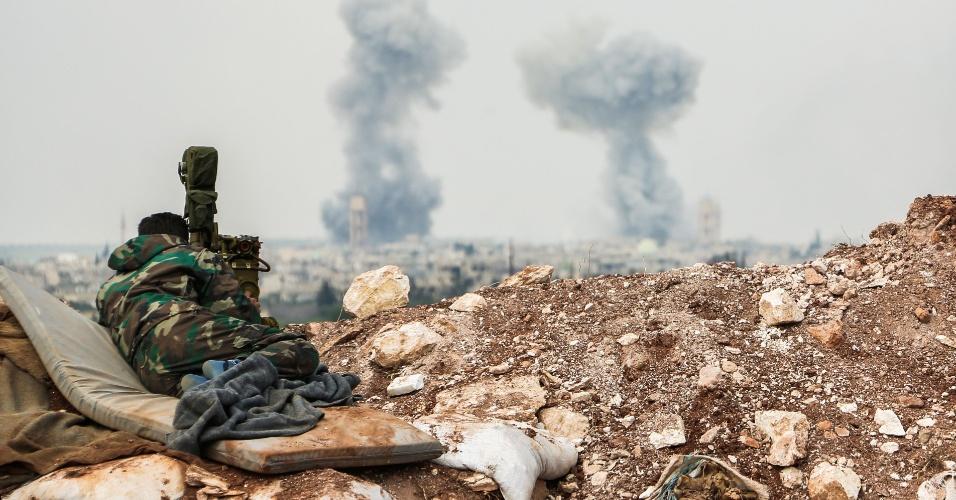 2.abr.2017 - Atirador das forças sírias observa a fumaça no horizonte próximo à cidade de Qumhanah no interior da província de Hama