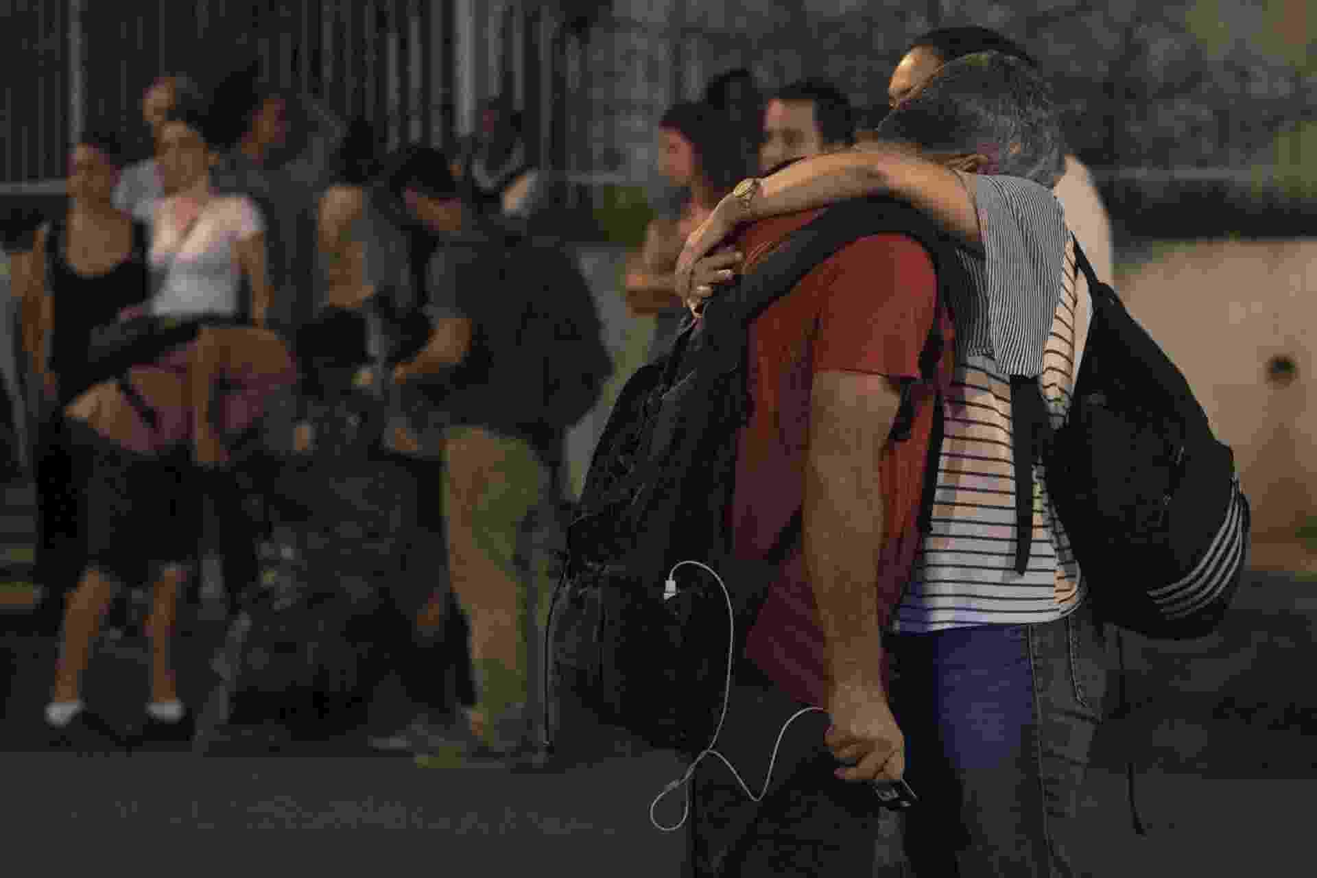 15.mar.2018 - Amigos e parentes da vereadora Marielle Franco (PSOL) se consolam no local onde a parlamentar foi assassinada a tiros no bairro do Estácio, no Rio de Janeiro, na noite da quarta-feira (14). Ela foi morta quando voltava de um evento na Lapa, centro do Rio - Mauro Pimentel/AFP