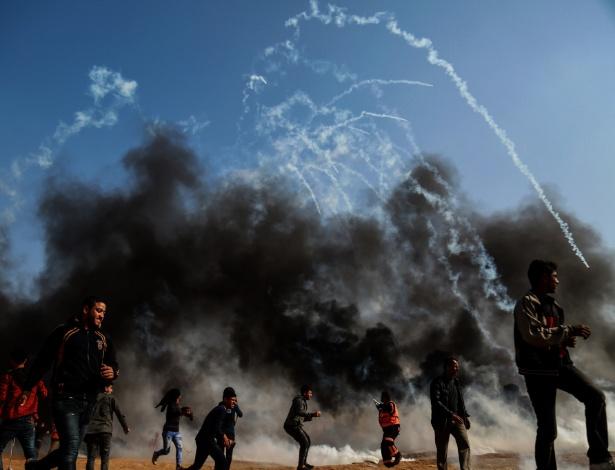 27.abril.2018 - Manifestantes palestinos correm para se protegerem de gás lacrimogêneo disparado por soldados israelenses na cidade de Gaza