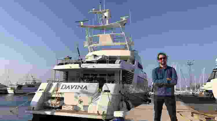 Jamie Bartlett, autor desta reportagem e do podcast The Missing Cryptoqueen, diante do iate de Ruja - BBC - BBC