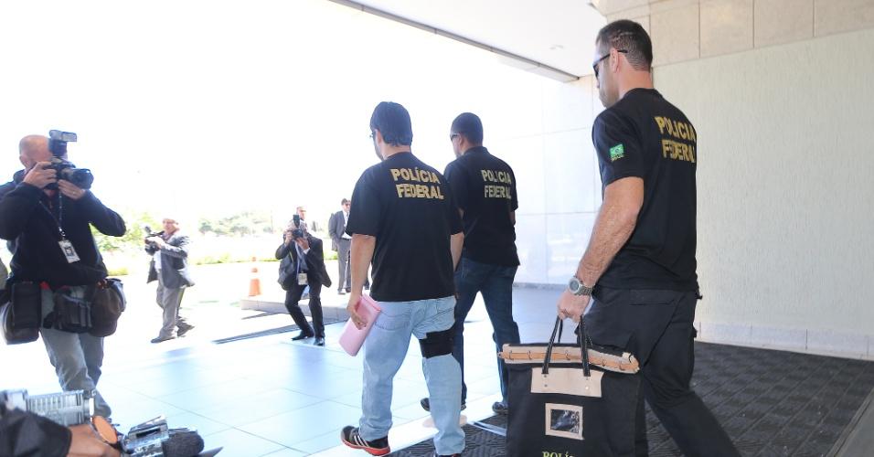13.ago.2015 - Policiais federais deixam prédio do setor hoteleiro Sul, em Brasília, com documentos apreendidos no escritório da JD2, durante a 18ª fase da Operação Lava Jato, deflagrada nesta manhã pela PF (Polícia Federal). A operação identificou a existência de um esquema de pagamento de valores ilícitos referente à concessão de empréstimo consignado por meio do Ministério do Planejamento