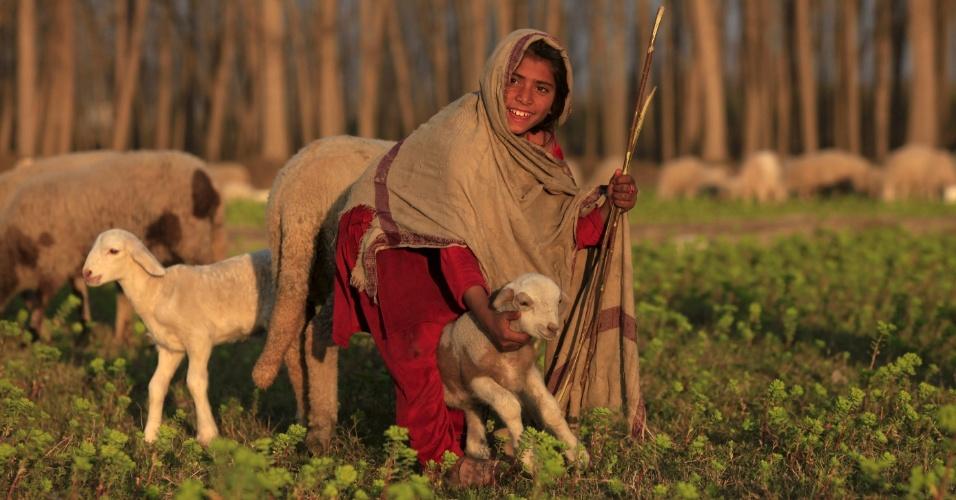 17.fev.2016 - Menina segura filhote de ovelha em um campo em Nowshera, no Paquistão