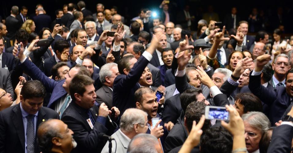 """16.mar.2016 - Deputados gritam pela renúncia da presidente Dilma Rousseff, durante sessão da Câmara, após saberem que o juiz federal Sergio Moro incluiu no inquérito que tramita em Curitiba uma conversa telefônica entre o ex-presidente Lula e a presidente Dilma Rousseff, no qual ela diz que encaminhará a ele o """"termo de posse"""" de ministro. Dilma diz a Lula que o termo de posse só seria usado """"em caso de necessidade"""""""