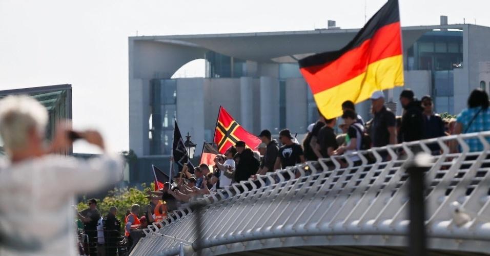 """7.mai.2016 - Cerca de 2 mil manifestantes de extrema-direita marcham em Berlim, Alemanha, para exigir a renúncia da chanceler Angela Merkel, por permitir que mais de um milhão de imigrantes do Oriente Médio entrassem no país desde o ano passado. Os manifestantes gritaram """"Merkel deve ir"""" e seguraram cartazes com dizeres como: """"Islâmicos não são bem-vindos"""""""
