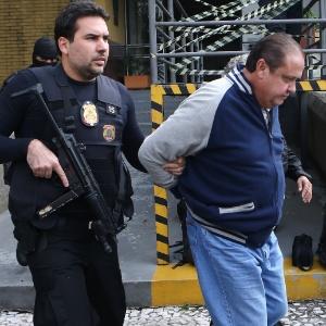O ex-tesoureiro do PP (Partido Progressista), João Claudio Genú (centro), é conduzido para a realização de exame de corpo de delito