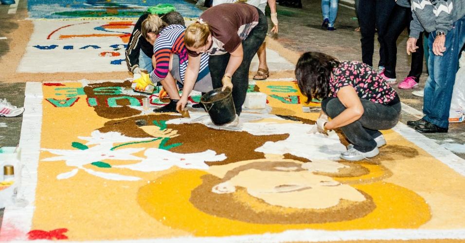 26.mai.2016 - Voluntários preparam o tradicional tapete decorativo de Corpus Christi para a passagem da procissão em Matão, no interior de São Paulo