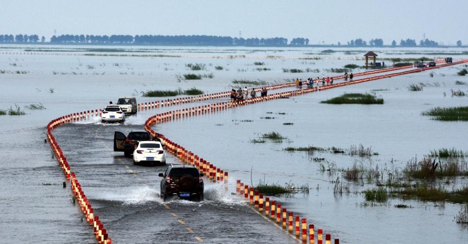 23.jun.2016 - Veículos trafegam por estrada inundada dentro de reserva natural em Yongxiu, na província de Jiangxi, localizada no leste da China. Chuvas torrenciais nos últimos dias deixaram várias regiões da reserva alagadas