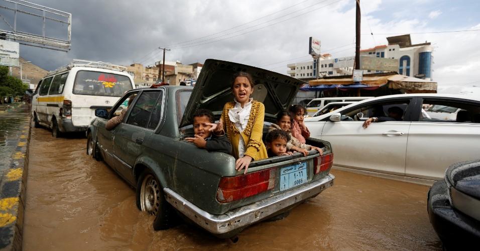 1º.ago.2016 - Crianças são colocadas no porta-malas de um carro para deixar bairro inundado em Sanaa, no Iêmen.
