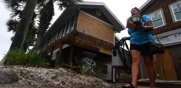 Moradora leva seus pertences ao deixar sua casa por causa da aproximação do furacão Matthew, na Flórida