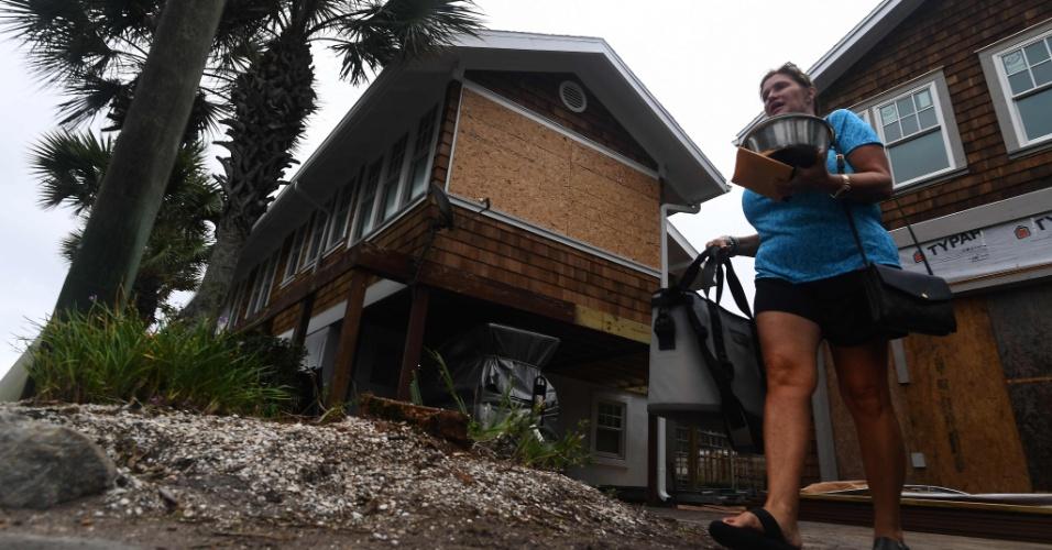 5.out.2016 - Moradora leva seus pertences ao deixar sua casa por causa da aproximação do furacão Matthew, na Flórida
