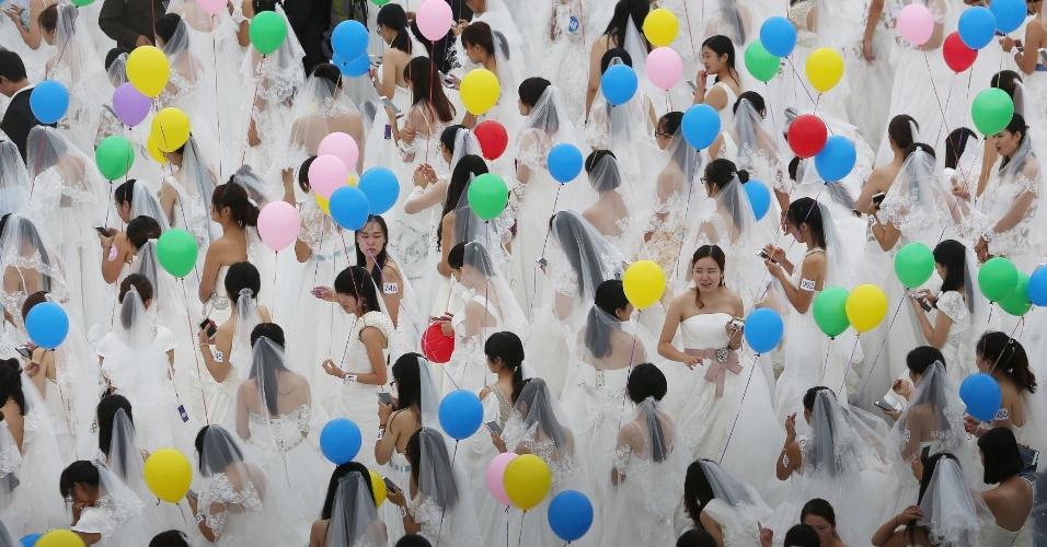 9.out.2016 - Mulheres de vestido de noiva seguram bexigas durante um evento de casamentos em Suzhou, na província de Jiangsu, China, e tentam bater o recorde do maior número de pessoas vestidas de noiva
