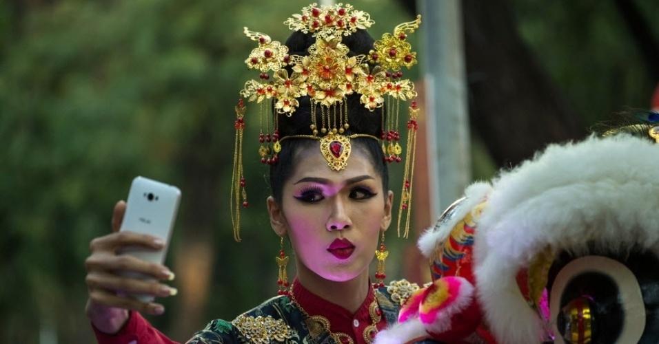 28.jan.2016 - Tailandesa faz uma pausa para tirar uma selfie durante as apresentações das celebrações do Ano Novo Chinês, que começa neste sábado, em Bancoc