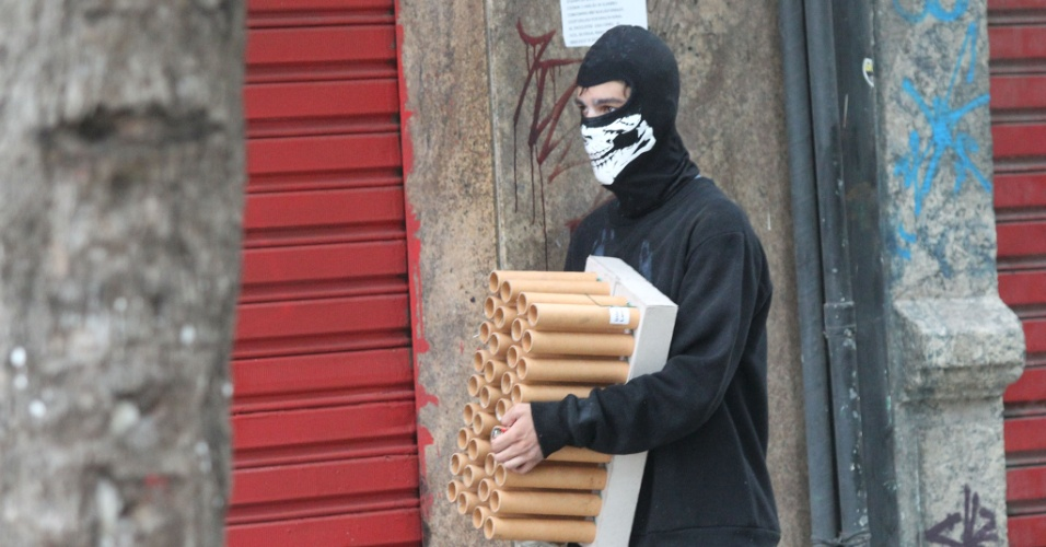 9.fev.2017 - Homem com o rosto coberto carrega cangalha de rojões durante confronto entre policiais e manifestantes nos arredores da Alerj, no Centro do Rio