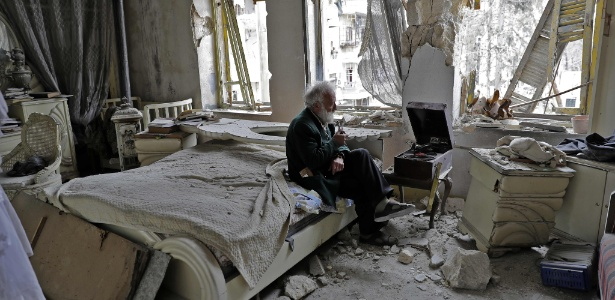 Mohammad Mohiedine Anis, 70, fuma seu cachimbo enquanto ouve música em seu quarto destruído em Aleppo