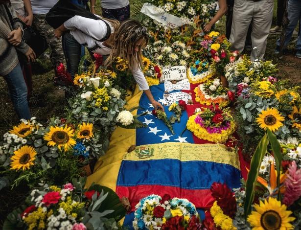 Mulher coloca flores no túmulo do líder rebelde Óscar Perez, em El Hatillo, na Venezuela