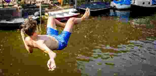 27.jul.2018 - Garoto se joga em canal de Amsterdã para driblar o calor na cidade nesta sexta - Remko de Wall/AFP Photo - Remko de Wall/AFP Photo