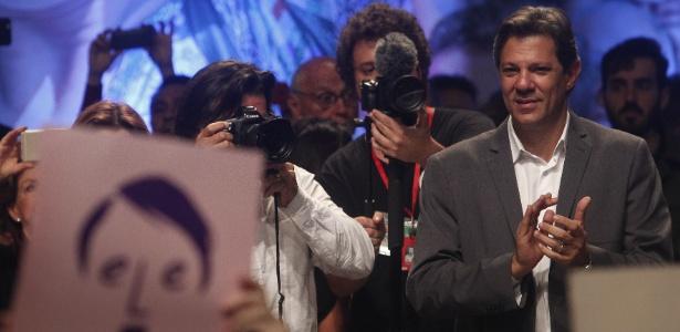 """Haddad (PT) participa de ato no Tuca, em São Paulo. Na plateia, um militante segura um cartão com o rosto de Bolsonaro (PSL) e a frase """"ele não"""""""