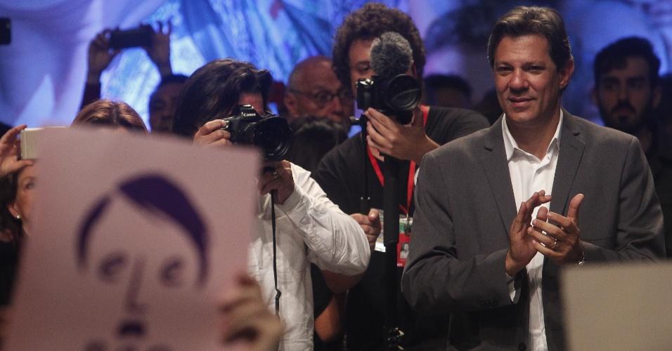 """22.out.2018 - Presidenciável Fernando Haddad (PT) participa de ato no Tuca, Teatro da PUC-SP, em São Paulo. Na plateia, um militante segura um cartão com o rosto do também candidato Jair Bolsonaro (PSL) e a frase """"ele não"""""""