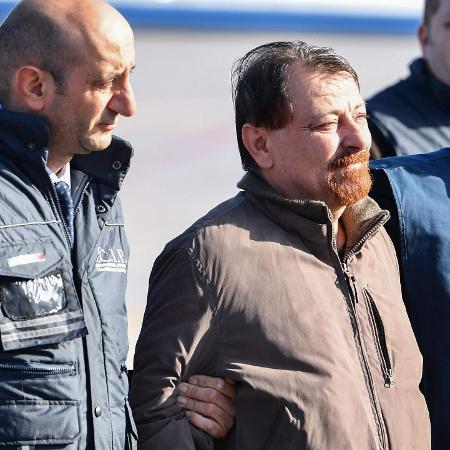 14.jan.2019 - Cesare Battisti é conduzido por policiais italianos ao desembarcar no aeroporto de Ciampino, em Roma - Alberto Pizzoli/AFP