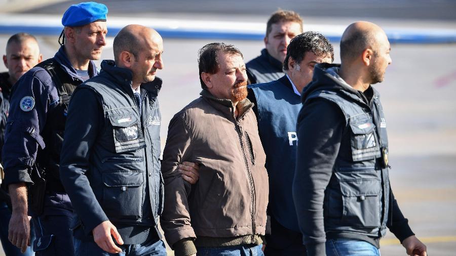 Battisti é conduzido por policiais italianos ao desembarcar no aeroporto de Ciampino, em Roma - Alberto Pizzoli/AFP