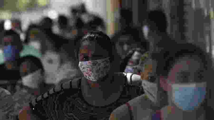 Fila de pessoas em busca de receber o auxílio emergencial em agência da Caixa no Rio de Janeiro na segunda-feira (27) - RICARDO MORAES