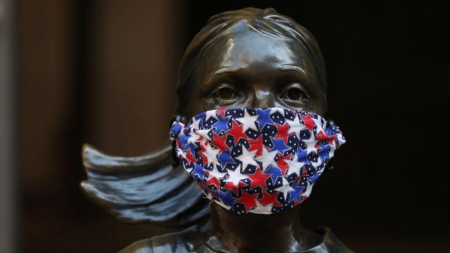 """Estátua da """"Fearless Girl"""", em Nova York (EUA), usa máscara para se """"proteger"""" do coronavírus - Rob Kim/Getty Images"""