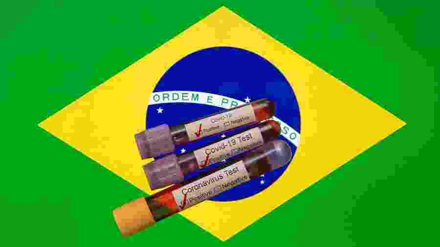 Testes de coronavírus em frente à bandeira do Brasil - Mehmet Emin Menguarslan / Anadolu Agency