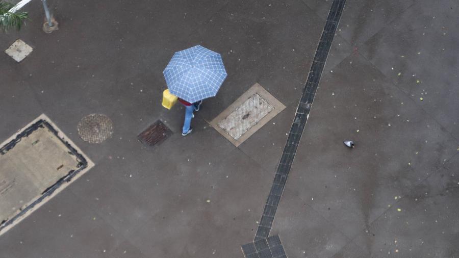 Pedestres se protegem do frio e da chuva que atinge a região central cidade de São Paulo - LECO VIANA/ESTADÃO CONTEÚDO