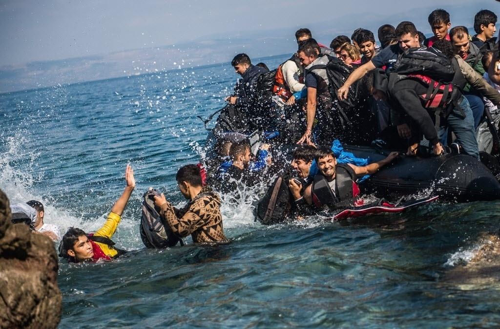 4.out.2015 - Ao se aproximarem da costa da ilha grega de Lesbos, imigrantes vindos da Turquia saltam na água para alcançarem a terra firme. De acordo com autoridades gregas, só em agosto 100 mil refugiados chegaram às ilhas gregas