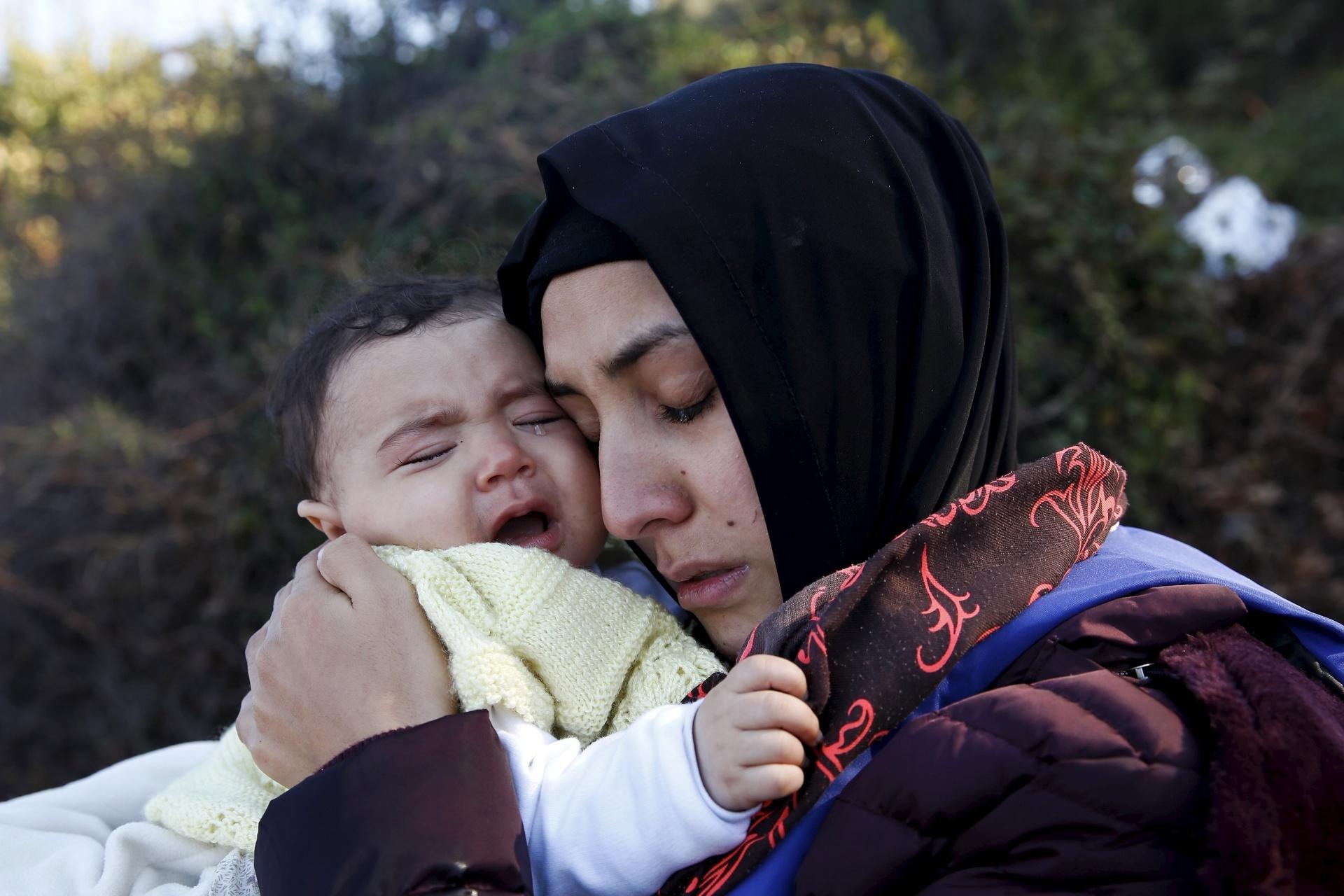 27.out.2015 - Mãe síria abraça bebê chorando depois de conseguir chegar à ilha grega de Lesbos. Durante o mês de outubro, a chegada de refugiados e imigrantes através do mar Mediterrâneo à Europa superaram as registradas em qualquer mês anterior, com 179.470, disse nesta terça-feira (27) a Acnur (Agência das Nações Unidas para os Refugiados)