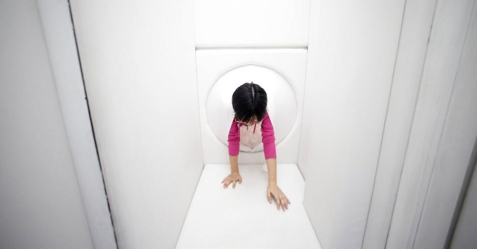 """22.abr.2016 - Uma funcionário vivencia a experiência de """"nascer"""" de um útero gigante feito de látex, no Pavilhão Vida e Morte, em Xangai, na China"""