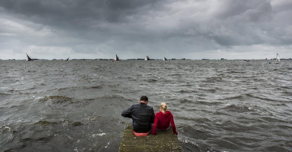 5.ago.2016 - Um casal assiste a uma competição de veleiros em Elahuizen, na Holanda