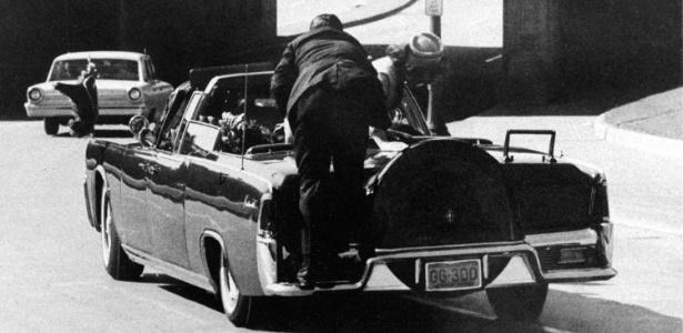 """22.nov.1963 - O agente secreto Clint Hill (terno escuro) puxa a primeira-dama Jacqueline Kennedy (dir.) de volta ao banco após o presidente John F. Kennedy ser baleado, em Dallas - James W. """"Ike"""" Altgens/ AP"""