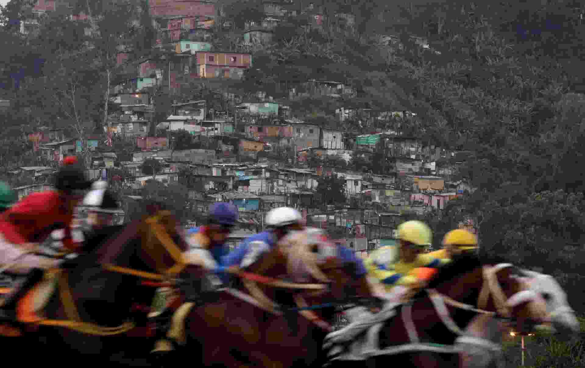 8.ou.2017 - Competidores participam de uma corrida de cavalos, com uma favela em segundo plano no Hipódromo La Rinconada, Caracas, Venezuela - RICARDO MORAES/REUTERS