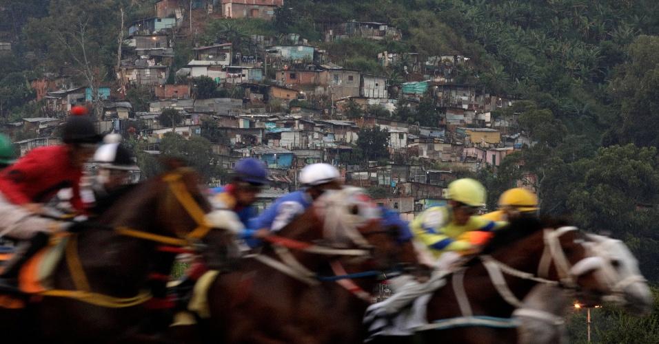 8.ou.2017 - Competidores participam de uma corrida de cavalos, com uma favela em segundo plano no Hipódromo La Rinconada, Caracas, Venezuela
