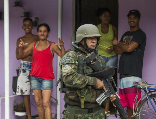 Moradores observam patrulha no primeiro dia da intervenção federal no Rio de Janeiro