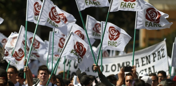 Simpatizantes e integrantes do antigo grupo guerrilheiro agitam bandeiras com o logo do partido político Farc, em Bogotá, Colômbia - Raul Arboleda/ AFP
