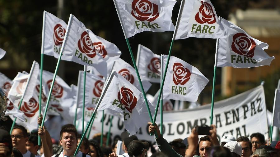 1.set.2017 - Simpatizantes e integrantes do antigo grupo guerrilheiro agitam bandeiras com o logo do partido político Farc, em Bogotá, Colômbia - Raul Arboleda/ AFP